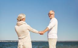Happy senior couple holding hands summer beach Stock Photo