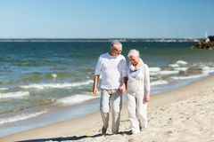 Happy senior couple holding hands on summer beach. Family, age, travel, tourism and people concept - happy senior couple holding hands and walking on summer Stock Images