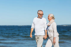 Happy senior couple holding hands on summer beach. Family, age, travel, tourism and people concept - happy senior couple holding hands and walking on summer Royalty Free Stock Images