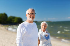 Happy senior couple holding hands on summer beach. Family, age, travel, tourism and people concept - happy senior couple holding hands and walking on summer Royalty Free Stock Image