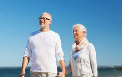 Happy senior couple holding hands on summer beach. Family, age, travel, tourism and people concept - happy senior couple holding hands and walking on summer Stock Photo