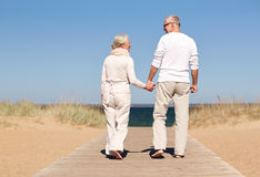 Happy senior couple holding hands on summer beach. Family, age, travel, tourism and people concept - happy senior couple holding hands and walking on summer Royalty Free Stock Photography