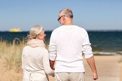 Happy senior couple holding hands on summer beach. Family, age, travel, tourism and people concept - happy senior couple holding hands and walking on summer Royalty Free Stock Photo