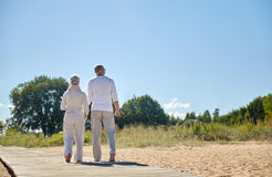 Happy senior couple holding hands on summer beach. Family, age, travel, tourism and people concept - happy senior couple holding hands and walking on summer Royalty Free Stock Photos
