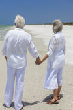 Happy Senior Couple Holding Hands on Tropical Beach. Rear view of happy senior men and women couple holding hands together looking out to sea on a deserted Royalty Free Stock Photo