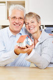 Happy senior couple holding house Stock Photos