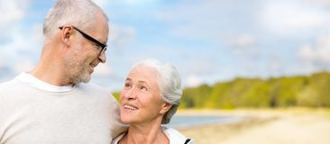 Happy senior couple hugging over beach background. Old age, retirement and people concept - happy senior couple hugging over beach background royalty free stock photo
