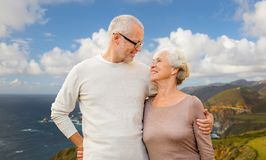 Happy senior couple hugging over big sur coast. Old age, tourism, travel and people concept - happy senior couple hugging over bixby creek bridge on big sur royalty free stock photos