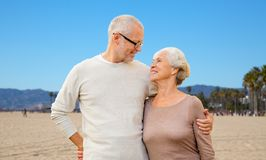 Happy senior couple hugging over venice beach. Old age, travel and tourism concept - happy senior couple hugging over venice beach background in california stock photo