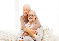 Happy senior couple hugging on sofa at home Royalty Free Stock Images