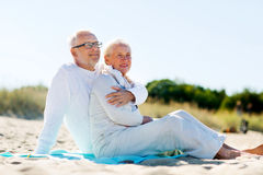Happy senior couple hugging on summer beach. Family, age, travel, tourism and people concept - happy senior couple hugging on summer beach Stock Images