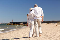 Happy senior couple hugging on summer beach. Family, age, travel, tourism and people concept - happy senior couple hugging on summer beach Royalty Free Stock Photos