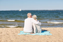 Happy senior couple hugging on summer beach. Family, age, travel, tourism and people concept - happy senior couple sitting on plaid and hugging on summer beach Royalty Free Stock Image