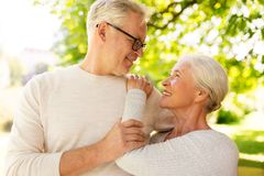 Happy senior couple hugging at summer park. Old age, love and people concept - happy senior couple hugging at summer park Royalty Free Stock Photo