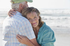 Happy senior couple hugging on sunny beach stock photos