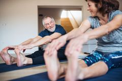 A senior couple indoors at home, doing exercise on the floor. A happy senior couple indoors at home, doing exercise on the floor stock photos