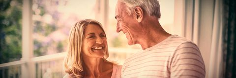 Happy senior couple interacting with each other in balcony stock photography