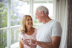 Happy senior couple interacting with each other in balcony. At home Stock Photo