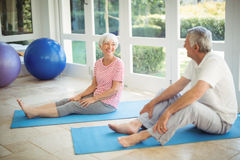 Happy senior couple interacting while performing exercise on exercise mat. At home Royalty Free Stock Image