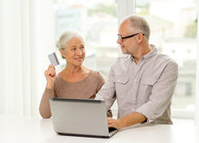 Happy senior couple with laptop and credit card Stock Images