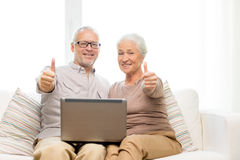 Happy senior couple with laptop at home Stock Photo