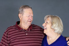 Happy senior couple laughing. Together, studio shot over grey background Stock Images