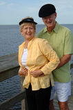 Happy senior couple laughing. A happy senior couple laughing standing outside on a boardwalk royalty free stock photography