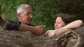 Happy senior couple leaning on a tree trunk. CU. Portrait of middle-aged men and women who stand leaning on the tree trunk in the forest stock footage