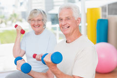 Happy senior couple lifting dumbbells in gym Royalty Free Stock Photos