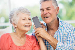 Happy senior couple listening to smartphone Stock Image