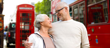 Happy senior couple on london street in england. Family, age, tourism, travel and people concept - happy senior couple over london city street in england Stock Images