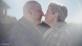 Happy senior couple look at each other, touching noses and old bald man kiss womans forehead with love, passion and