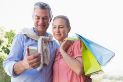 Happy senior couple looking at smartphone holding shopping bags Royalty Free Stock Photo
