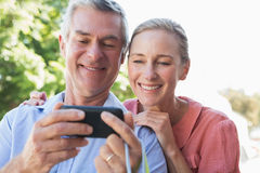 Happy senior couple looking at smartphone Royalty Free Stock Photos