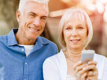 Happy senior couple looking at smartphone Royalty Free Stock Images