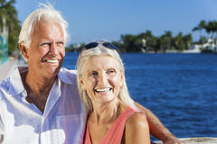 Happy Senior Couple Looking to Tropical Sea or River. Happy senior men and women romantic couple together looking out to tropical sea or river with bright clear Royalty Free Stock Photo