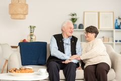 Happy senior couple on sofa. Happy senior couple in love showing tenderness and enjoying their time together holding hands and sitting on sofa with blue blanket royalty free stock images