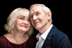 Happy senior couple in love standing together on black Stock Images