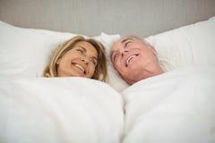 Happy senior couple lying on bed Stock Photography
