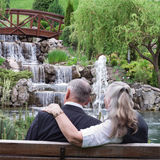 Happy senior couple lying in park near waterfall royalty free stock photos