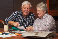 Happy senior couple making a scrapbook. Happy senior married couple sharing memories while working on family photo  album together. Horizontal format Stock Photos