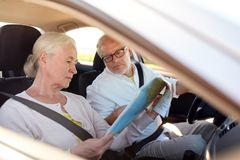 Happy senior couple with map driving in car Royalty Free Stock Photo