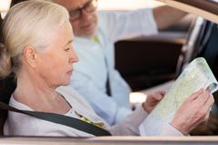 Happy senior couple with map driving in car. Road trip, travel and old people concept - happy senior couple with map driving in car Royalty Free Stock Photography