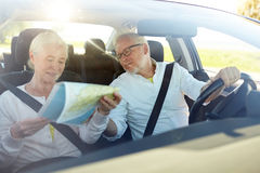 Happy senior couple with map driving in car Stock Image