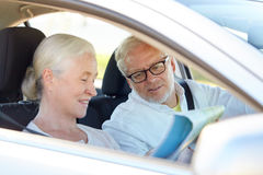 Happy senior couple with map driving in car. Road trip, travel and old people concept - happy senior couple with map driving in car Royalty Free Stock Images