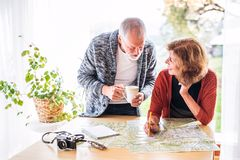 Senior couple with map at home, making plans. Stock Image