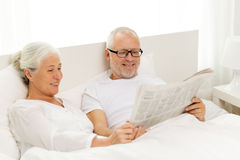 Happy senior couple with newspaper in bed Stock Photography