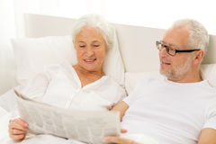 Happy senior couple with newspaper in bed Royalty Free Stock Image