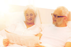 Happy senior couple with newspaper in bed Royalty Free Stock Photo