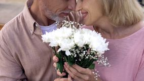 Happy senior couple nuzzling, holding flowers bunch together, anniversary date. Stock photo stock image